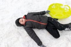 Um menino de sete anos de encontro velho na neve e guardar um trenó plástico verde em sua mão Conceito de atividades do inverno,  fotografia de stock