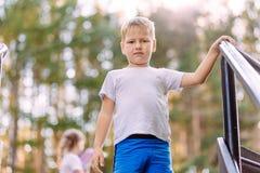Um menino de sete anos louro em um t-shirt branco e olhares azuis do short na câmera em um fundo natural borrado fotografia de stock