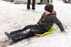 Um menino de sete anos velho monta a corrediça, abaixo do monte no trenó verde do gelo Conceito de atividades, de recreação e de  foto de stock