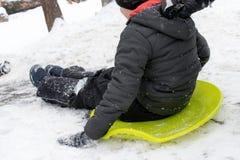 Um menino de sete anos velho monta a corrediça, abaixo do monte no trenó verde do gelo Conceito de atividades, de recreação e de  imagem de stock