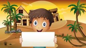 Um menino de sorriso no deserto com um signage vazio Fotografia de Stock