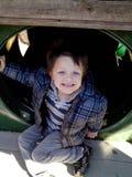 Um menino de sorriso no jogo no campo de jogos Fotografia de Stock Royalty Free