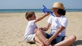 Um menino de sorriso pequeno joga com um plano que descreve o voo O bebê e a mãe são descansar, sentando-se na costa arenosa na vídeos de arquivo