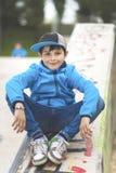 Um menino de sorriso que senta-se nos trilhos de pedra com os braços em seus pés imagem de stock