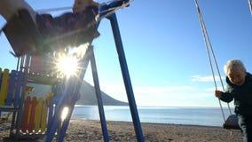 Um menino de três anos e uma menina de 6 anos que balançam em um balanço em uma manhã ensolarada na costa vídeos de arquivo