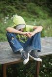 Um menino desabrigado senta-se em um banco com sua cabeça curvada para baixo fotos de stock