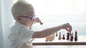 Um menino do albino em uma camisa branca está jogando a xadrez em uma tabela filme