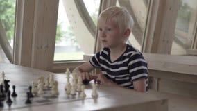 Um menino do albino joga a xadrez em um clube de xadrez video estoque