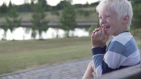 Um menino do albino senta o riso alegremente vídeos de arquivo