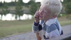 Um menino do albino senta o riso alegremente Ri e cobre sua boca com o riso video estoque