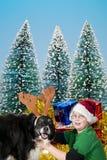 Um menino do Natal e seu cão da rena Fotos de Stock