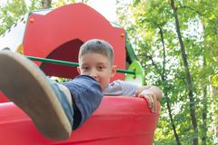Um menino do preteen que joga em um campo de jogos do ` s das crianças imagem de stock