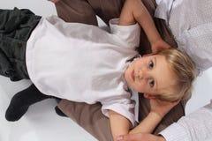 Um menino doce adorável que encontra-se no regaço do seu paizinho fotos de stock