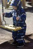 Um menino dos anos de idade 2 que joga com um balanço Fotos de Stock