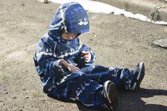 Um menino dos anos de idade 2 que senta-se e que olha em suas mãos Fotografia de Stock