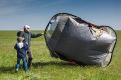 Um menino e um homem em um campo vasto com uma barraca A barraca funde o vento fotografia de stock