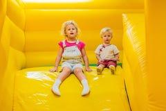 Um menino e um passeio da menina de uma corrediça inflável foto de stock royalty free