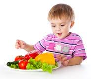 Um menino e a placa dos vegetais Imagem de Stock