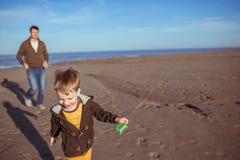 Um menino e seu paizinho estão correndo na areia Fotografia de Stock