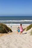 Um menino e um título da menina para a praia Foto de Stock