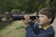 Um menino e um telescópio pequeno Imagens de Stock