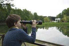 Um menino e um telescópio pequeno Foto de Stock Royalty Free