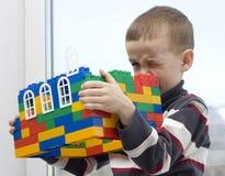 Um menino e uma casa do brinquedo. Fotografia de Stock Royalty Free