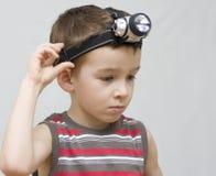 Um menino e uma lâmpada do capacete. Imagens de Stock