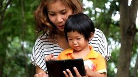 Um menino e uma mãe asiáticos estão jogando o jogo engraçado na tabuleta video estoque