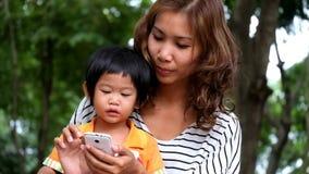 Um menino e uma mãe asiáticos estão jogando o jogo engraçado no telefone esperto no parque filme