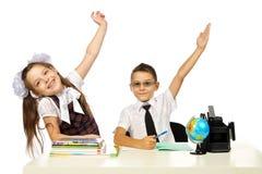Um menino e uma menina na mesa levantaram suas mãos Imagens de Stock