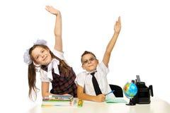 Um menino e uma menina na mesa levantaram suas mãos Imagens de Stock Royalty Free