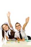 Um menino e uma menina na mesa levantaram suas mãos Fotografia de Stock Royalty Free