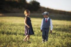 Um menino e uma menina no campo no por do sol iluminam-se Imagem de Stock Royalty Free
