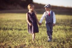 Um menino e uma menina no campo no por do sol iluminam-se imagens de stock royalty free