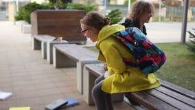 Um menino e uma menina, o irm?o e a irm?, os colegas e os amigos riem o assento em um banco perto da escola durante a ruptura video estoque