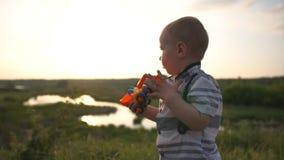 Um menino elegante bonito joga com um trator no por do sol no movimento lento vídeos de arquivo