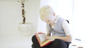 Um menino elegante do albino senta-se de pernas cruzadas no assoalho filme
