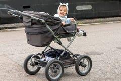Um menino em um carrinho de criança de bebê com orelhas engraçadas fotos de stock