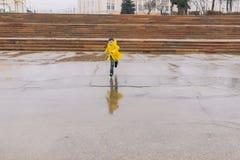 Um menino em um casaco amarelo brilhante corre abaixo da rua a uma poça foto de stock royalty free