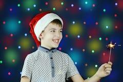 Um menino em um chapéu de Santa Claus e em um fogo de Bengal em suas mãos Imagem de Stock Royalty Free