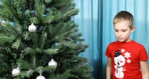 Um menino em um t-shirt com um boneco de neve veste acima uma árvore do ano novo em casa video estoque