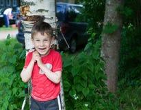 Um menino em um t-shirt vermelho foi para uma caminhada na jarda no verão fotos de stock royalty free