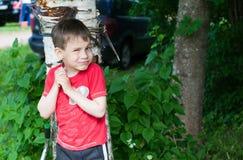 Um menino em um t-shirt vermelho foi para uma caminhada na jarda no verão imagens de stock royalty free