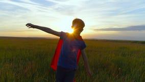Um menino em um traje do superman corre através do campo verde no por do sol Fotografia de Stock
