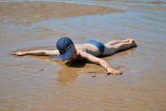 Um menino em troncos de natação e em um tampão encontra-se cara para baixo em um Sandy Beach após uma maré baixa, com seus braços imagens de stock royalty free