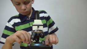 Um menino em um t-shirt listrado examina partes da planta sob um microscópio filme