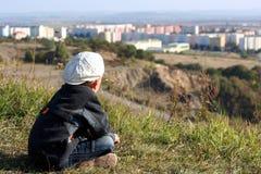 Um menino em um tampão branco está olhando na cidade Imagens de Stock Royalty Free