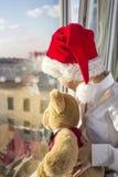 Um menino em um tampão vermelho olha para fora a janela Imagens de Stock