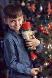 Um menino em uma árvore do ano novo com uma quebra-nozes Fotos de Stock Royalty Free